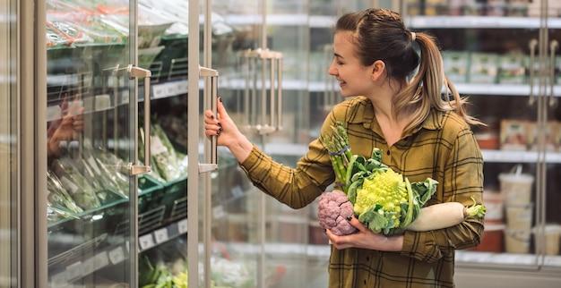 スーパーマーケットの女性。美しい若い女性は手で新鮮な有機野菜を保持し、スーパーマーケットで冷蔵庫を開きます。健康的な食事のコンセプトです。収穫 無料写真