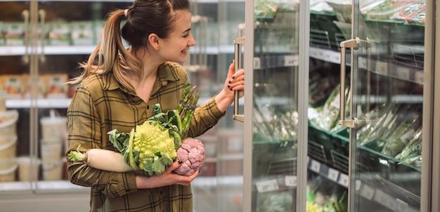 スーパーマーケットの女性。美しい若い女性は新鮮な有機野菜を手で保持し、スーパーで冷蔵庫を開きます 無料写真