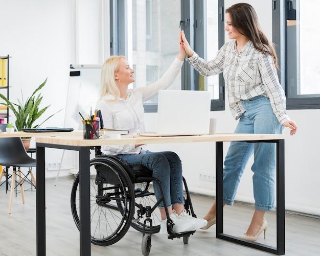 オフィスで彼女の女性の同僚をハイファイする車椅子の女性 無料写真