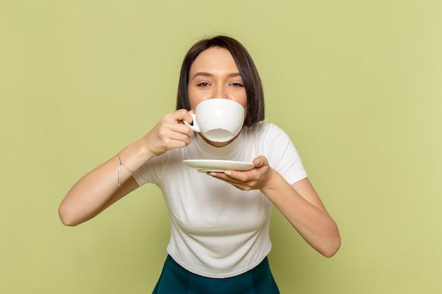 白いブラウスとお茶を飲んで緑のスカートの女性 無料写真