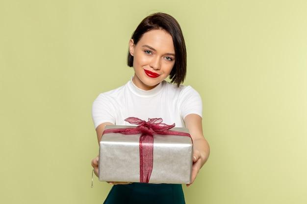 プレゼントボックスを保持している白いブラウスと緑のスカートの女性 無料写真