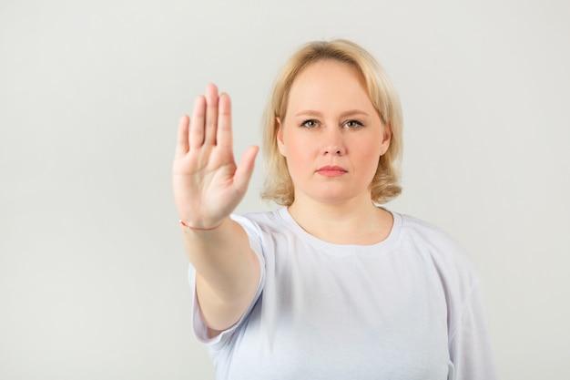 手ジェスチャーで白い背景に白いtシャツの女性 Premium写真