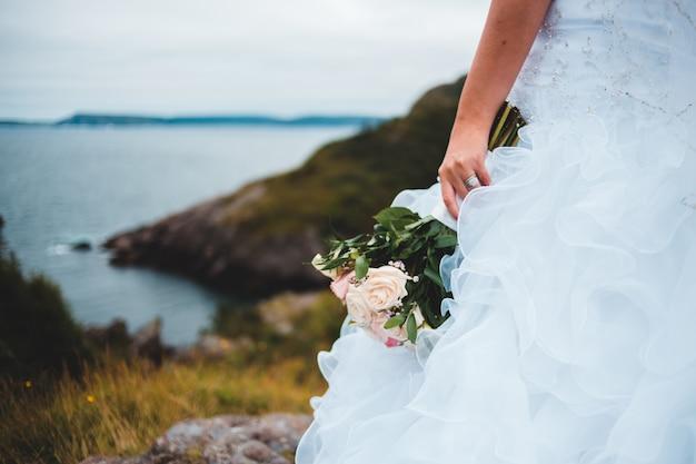 花の花束を保持している白いウェディングドレスを着た女性 無料写真