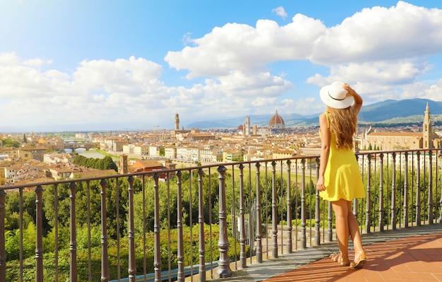 Женщина в желтом платье смотрит потрясающий панорамный вид на флоренцию, италия. полная длина счастливой веселой красивой девушки в тоскане. Premium Фотографии