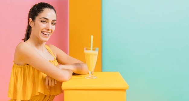 ジュースのグラスと黄色のドレスを着た女性 無料写真