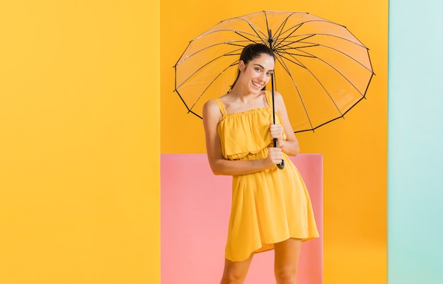 傘を持つ黄色のドレスを着た女性 無料写真