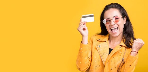 Женщина в желтой куртке держит пространство для копии кредитной карты Бесплатные Фотографии
