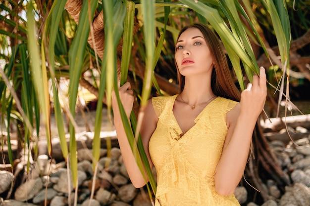 ヤシの木の近くに立っている黄色のサンドレスの女性 Premium写真