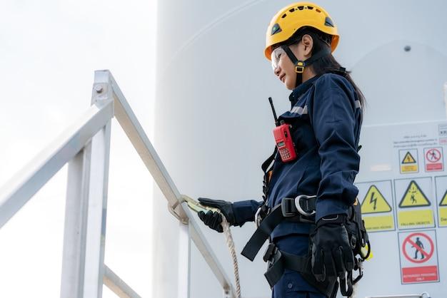 安全ハーネスと安全ラインを身に着けている女性検査エンジニア Premium写真