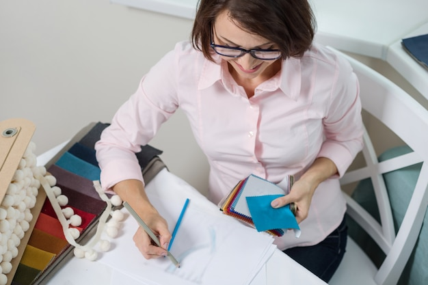 Woman interior designer, works with samples of fabrics Premium Photo