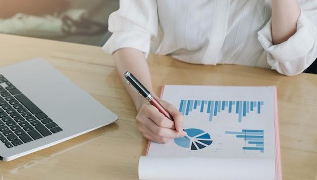 Женщина-консультант по инвестициям анализирует годовой финансовый отчет компании, балансовый отчет, работая с документами, графиками. Premium Фотографии