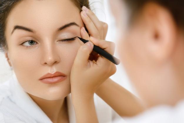 Женщина применяет подводка для глаз Premium Фотографии