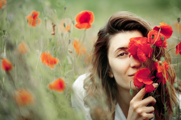 Woman is covering a face with a poppies flower bouquet Free Photo