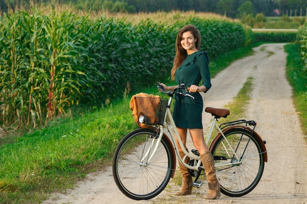 Woman is cycling by the country road in the cornfield Premium Photo