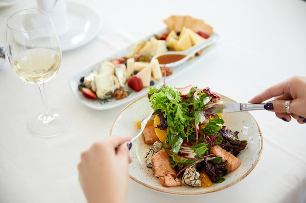 Woman is eating pork salad with lettuce, set cheese and a glass of wine Free Photo