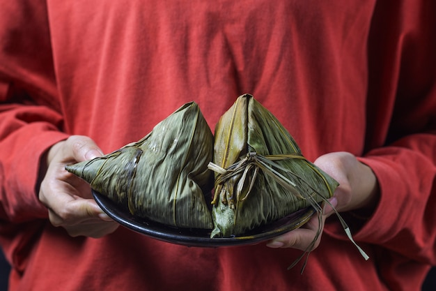 A woman is giving zongzi(rice dumpling) to others as a present on dragon boat festival, Premium Photo