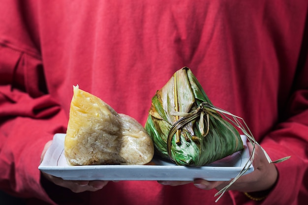 A woman is giving zongzi (rice dumpling) to others as a present on dragon boat festival Premium Photo