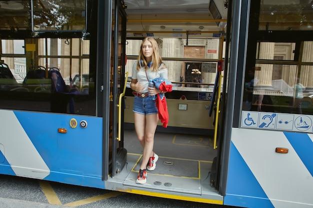 여자는 대중 교통 정류장에서 무궤도 전차를 나가고 있습니다. 프리미엄 사진