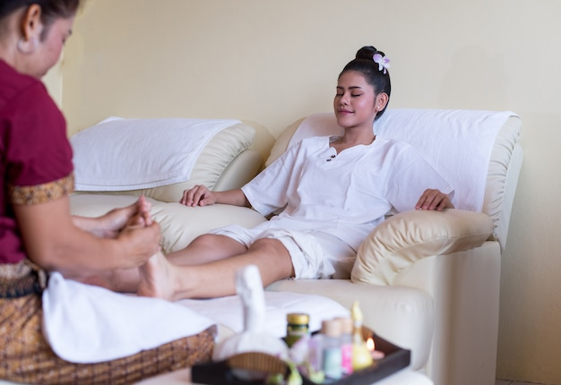 Woman is happy to enjoy in greflexology foot massage in wellness spa Premium Photo
