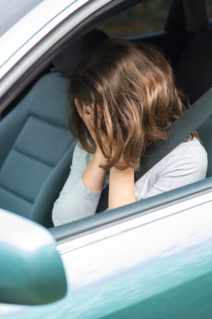 A woman is holding her head in the car. shock situation, accident. Premium Photo