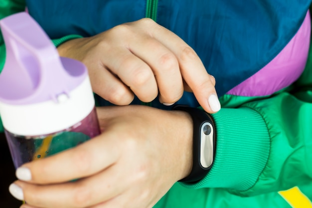 A woman is holding a water bottle for fitness and a fitness bracelet. in a sports bright green jacket for sports. healthy lifestyle and fitness concept Premium Photo