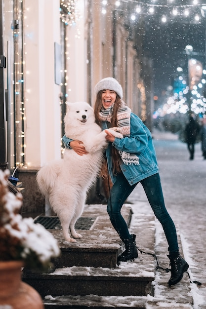 Woman is hugging her dog on a night street Free Photo