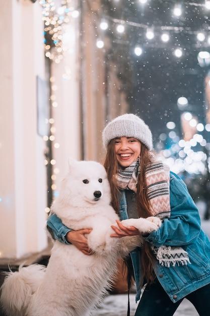 La donna sta abbracciando il suo cane in una strada di notte Foto Gratuite