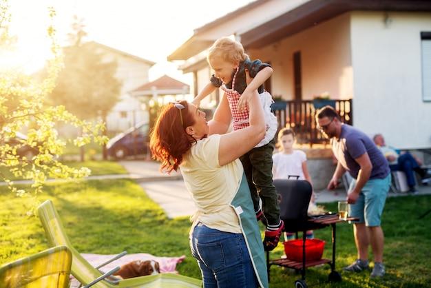 家族の残りが焼きている間、女性は彼女の豪華で陽気な幼児の男の子を高く持ち上げています。 Premium写真