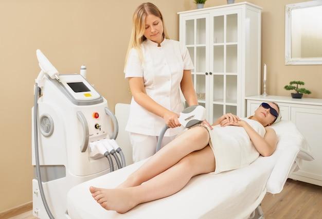 Женщина лежит на кушетке в медицинских очках в процедурном кабинете. Premium Фотографии