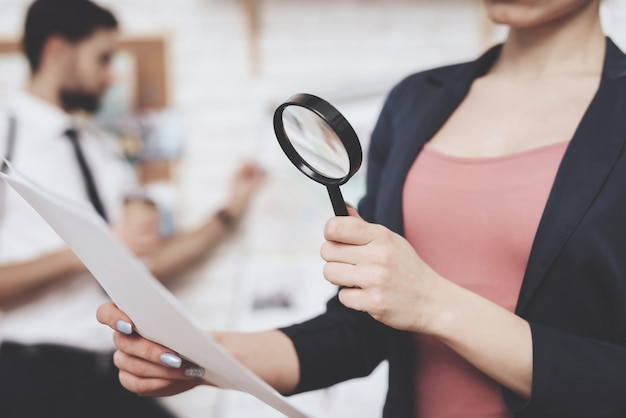 Woman is posing with paper and magnifying glass. Premium Photo