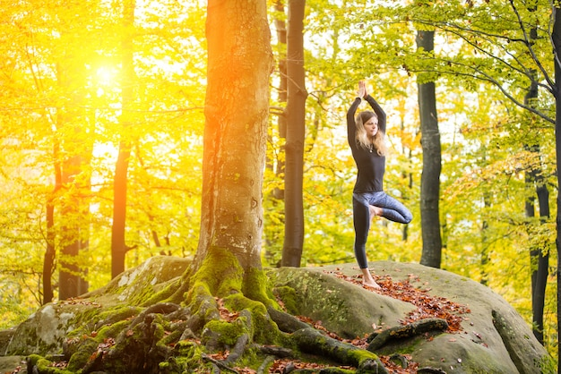 Woman is practicing yoga in autumn forest on the big stone Premium Photo