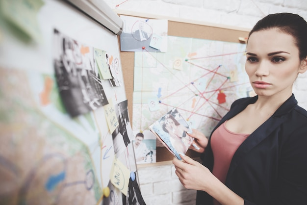 Woman is putting photos on clue map in office. Premium Photo