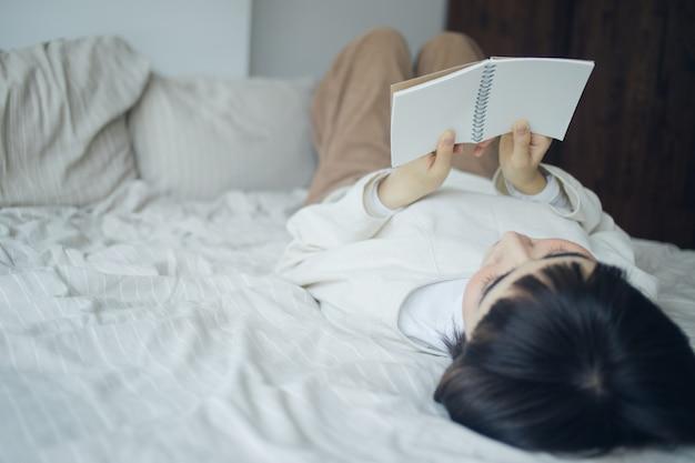 Женщина читает книгу в спальне. Premium Фотографии