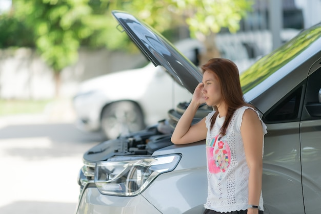 Женщина грустит из-за разбитой машины Premium Фотографии
