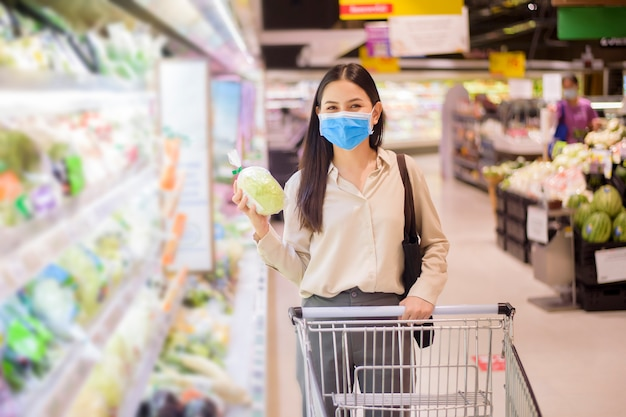女性はフェイスマスクとスーパーで買い物 Premium写真