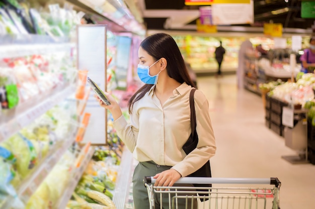 Woman is shopping in supermarket with face mask Premium Photo