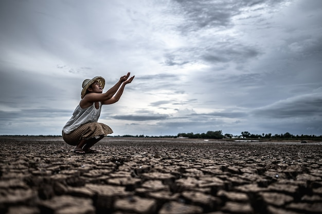 A woman is sitting asking for rain in the dry season, global warming Free Photo