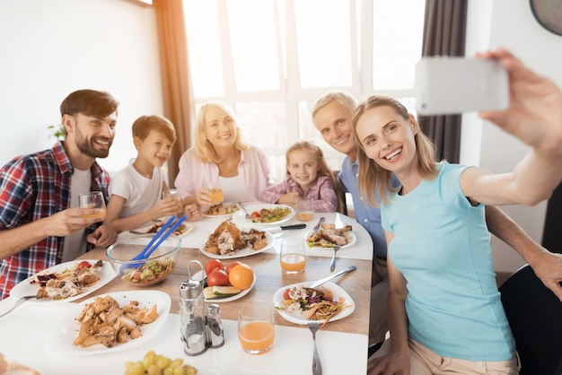 A woman is sitting at a festive table and making a selfie Premium Photo