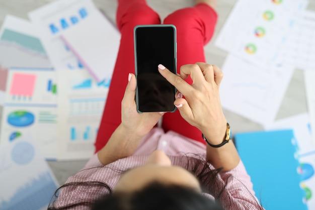 여자는 그녀의 손에 스마트 폰을 들고 상업 지표와 차트와 문서 주위에 바닥에 앉아있다 프리미엄 사진