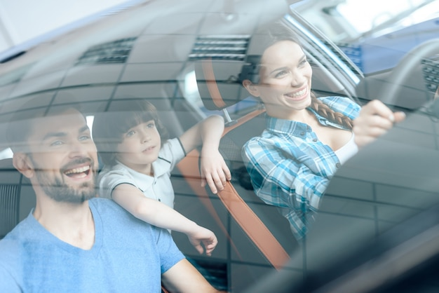 A woman is sitting at the wheel of a new car. Premium Photo