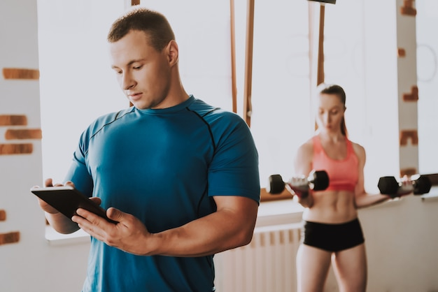 Woman is training in big gym with trainer Premium Photo