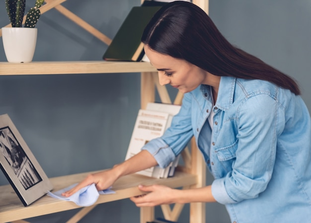 Woman is using a rag while cleaning furniture at home Premium Photo