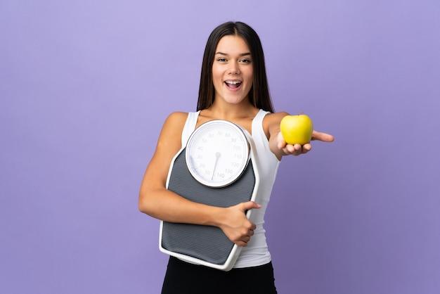 Женщина изолирована на фиолетовом, держа весы и предлагая яблоко Premium Фотографии