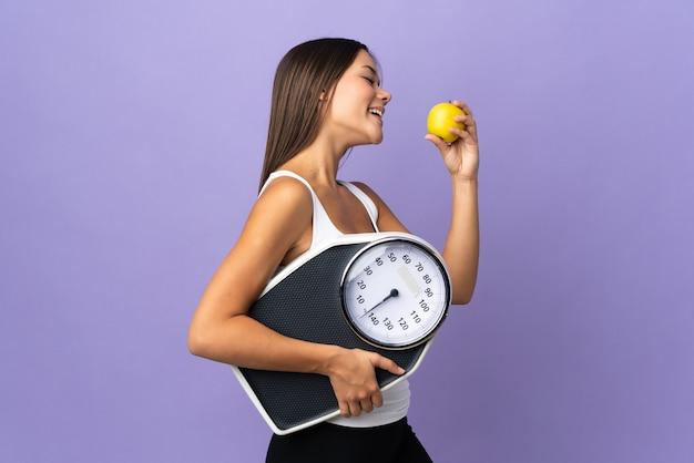 Женщина изолирована на фиолетовом с весами и с яблоком Premium Фотографии