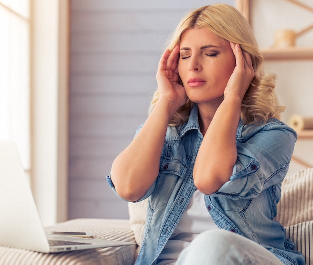 Woman in jeans shirt is having a headache. Premium Photo