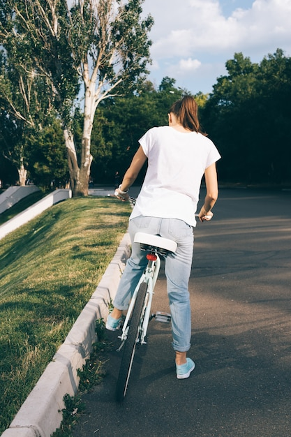 Woman in jeans and a t-shirt sits on a bicycle in the city park Premium Photo