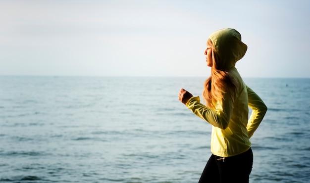 Woman jogging on a beach Free Photo
