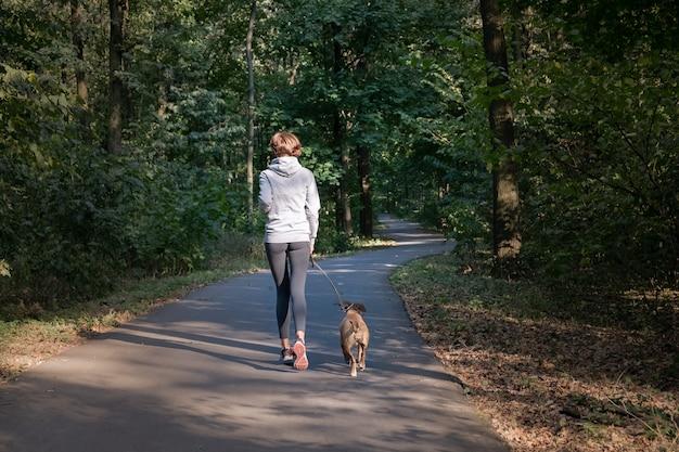 Женщина, бег с собакой в красивом лесу. молодая женщина с домашним животным делает беговые упражнения по пересеченной местности на свежем воздухе. Premium Фотографии