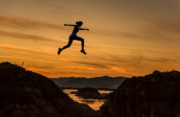 Woman jump through the gap between hill.woman jumping over cliff on sunset background Premium Photo