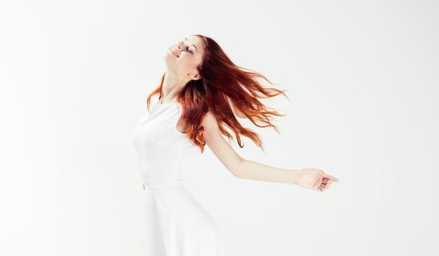 Женщина прыгает в белом платье изолированы Premium Фотографии